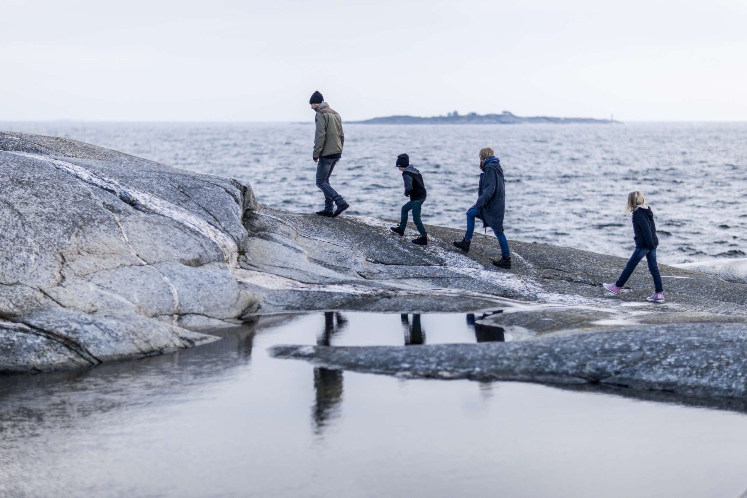 Family walking along the water: Who Can Your New Hire Bring to Sweden