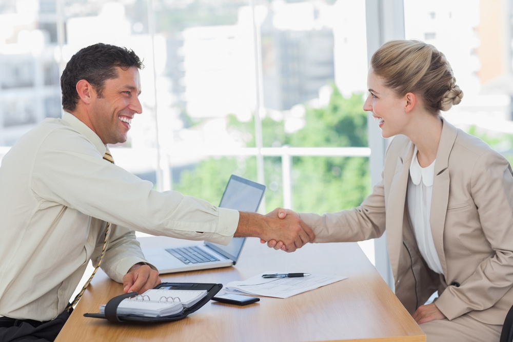 Blonde woman shaking hands while having an interview in office. How to work best with your relocation company