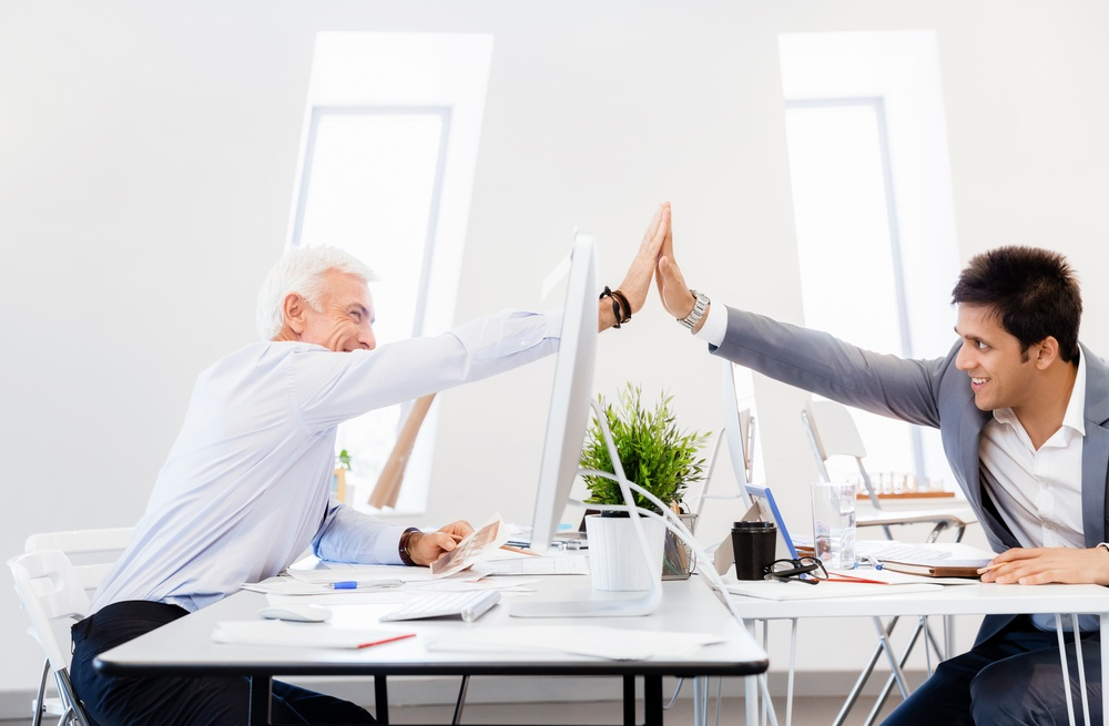 Businessmen in office cheering at their success: HOW TO EFFECTIVELY MANAGE A CULTURALLY AND AGE DIVERSE TEAM