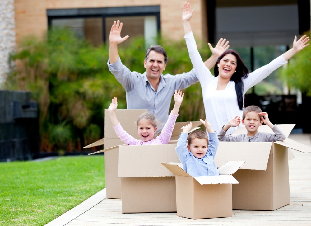 Happy family in cardboard boxes moving house: Tips to Help your Transferee with their move to Sweden