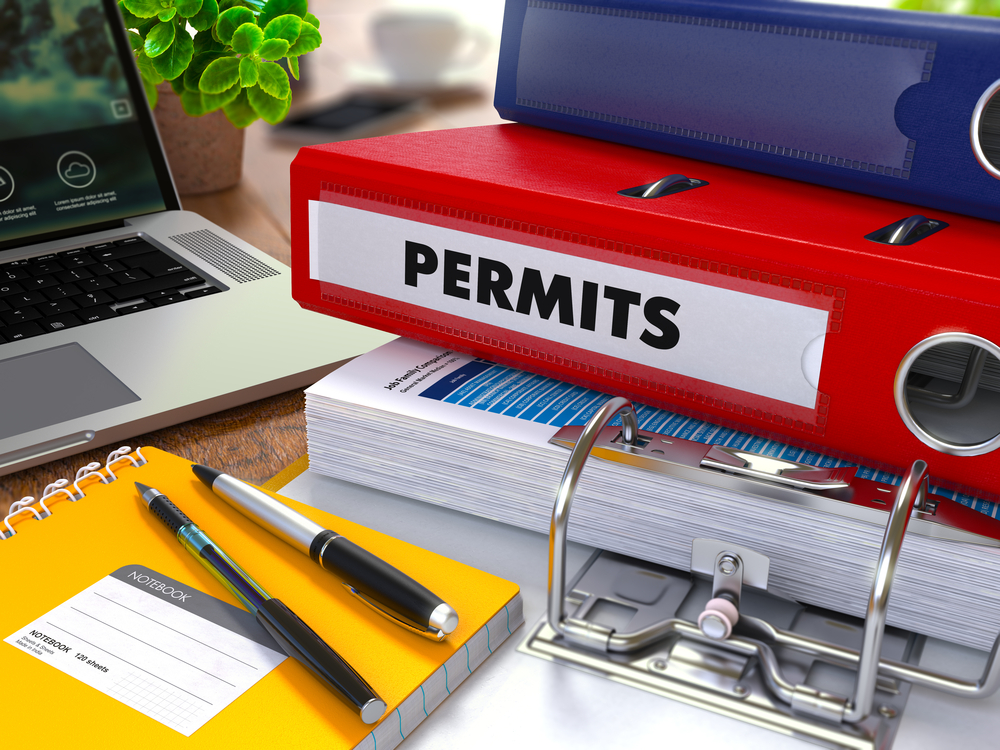 Red Ring Binder with inscription Permits on Background of Working Table with Office Supplies, Laptop, Reports. Toned Illustration. Business Concept on Blurred Background:MAKE SURE YOUR RECRUITERS ARE IN COMPLIANCE FOR WORK PERMIT HOLDERS!