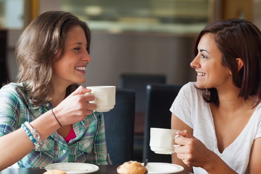2 women having coffee: 5 Swedish values your expats should know about