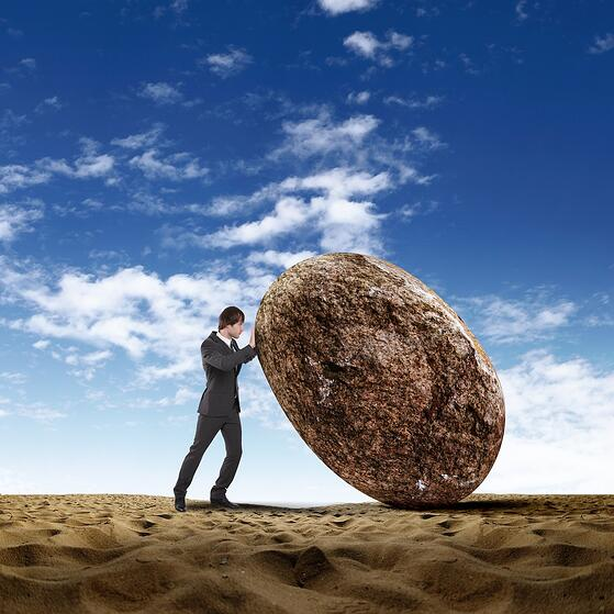 Image of businessman rolling a giant stone.jpeg