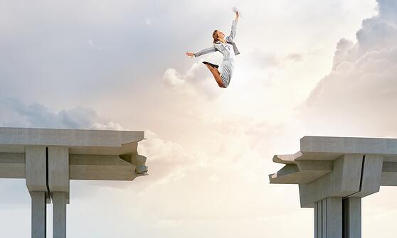 Young woman jumping over a gap in the bridge as a symbol of risk.jpeg