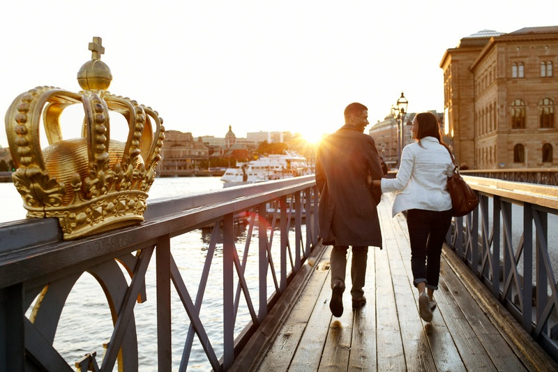Couple walking on bridge to Skeppsholmen Island: How to Help your Expat's Spouse
